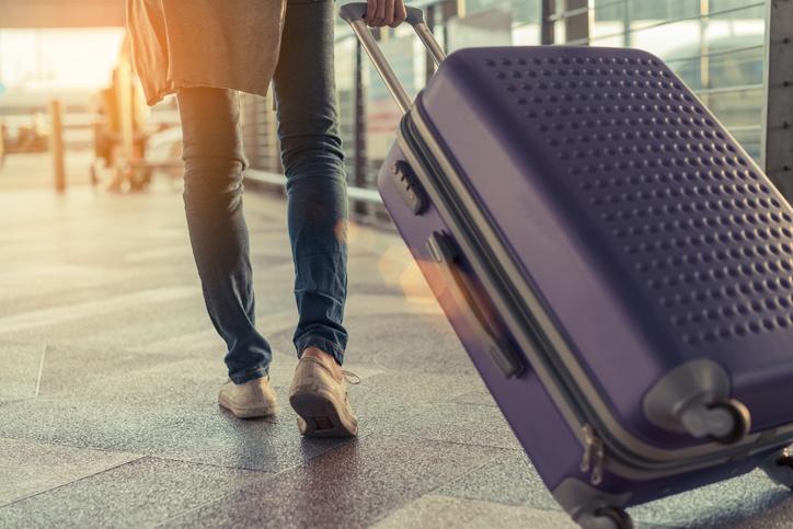 Traveler_pulling_purple_suitcase